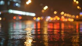 De kleurrijke verkeerslichten bokeh omcirkelt het nadenken in water op de straat van de nachtstad met kleine regendruppels langza stock footage