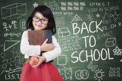 De kleuterschoolstudent houdt boek en appel Stock Afbeelding