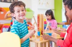 De kleuterschoolstudenten glimlachen wanneer het spelen van stuk speelgoed in speelkamer bij pres stock fotografie