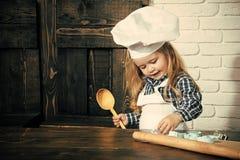 De kleutertijd is de keus van beroep Jongenskok in chef-kokhoed en schort in keuken royalty-vrije stock afbeelding