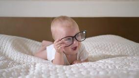 De kleutertijd, portret van leuk weinig kindjongen met grote blauwe ogen in glazen ligt op bed dichte omhooggaand stock videobeelden