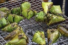 De kleverige rijst die in banaanbladeren wordt verpakt, die op de grill worden geroosterd is een populair voedsel in Thailand stock foto's