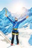 De klimmer bereikt de bovenkant van bergpiek Het beklimmen en mountaine royalty-vrije stock afbeeldingen