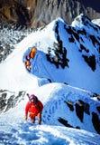 De klimmer bereikt de top van bergpiek Succes, vrijheid en geluk, voltooiing in bergen Het beklimmen van sportconcept stock foto