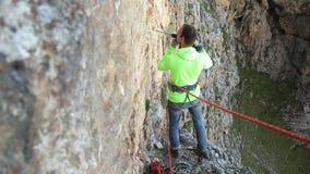 De klimmer boort rotsboor voor de organisatie van verzekering stock footage