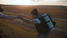 De klimmer die teammate helpen beklimmen, de man met de rugzak bereikte uit een helpende hand aan zijn vriend Wandelaar die vrien stock videobeelden