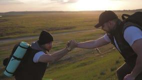 De klimmer die teammate helpen beklimmen, de man met de rugzak bereikte uit een helpende hand aan zijn vriend Wandelaar die vrien stock video