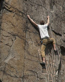 De klimmer die van de rots zich aan een klip vastklampt Stock Afbeelding