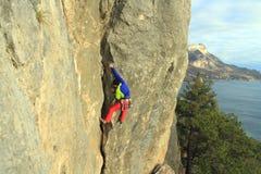 De klimmer die van de rots zich aan een klip vastklampt Stock Afbeeldingen