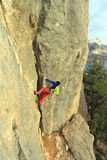 De klimmer die van de rots zich aan een klip vastklampt Royalty-vrije Stock Afbeelding