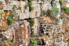 De klimmer die van de rots zich aan een klip vastklampt Royalty-vrije Stock Afbeeldingen