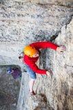 De klimmer in een helm beklimt omhoog Royalty-vrije Stock Foto