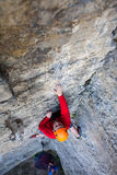 De klimmer in een helm beklimt omhoog stock fotografie