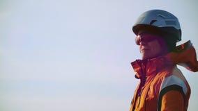 De klimmer een helm dragen en de glazen die hoog en genieten van mooie, Zonnige meningen kijken stock footage