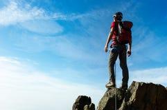 De klimmer komt op de top van een bergpiek aan Concepten: victo stock afbeelding