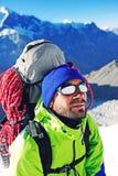 De klimmer met rugzakken bereikt de top van bergpiek succ Royalty-vrije Stock Fotografie