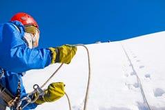 De klimmer met rugzakken bereikt de top van bergpiek Succes, vrijheid en geluk, voltooiing in bergen Actieve sport royalty-vrije stock foto