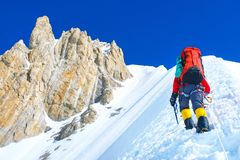 De klimmer met rugzakken bereikt de top van Succes van berg het piekeverest, vrijheid en geluk, voltooiing in bergen stock afbeelding