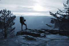De klimmer met wandelingsrugzak gaat naar berg Mannelijke sterke drager royalty-vrije stock afbeelding