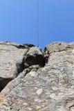 De klimmer van de meisjesrots beklimt op een rots Stock Afbeelding