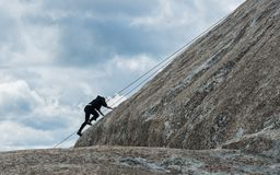 De klimmer van de studentenrots in silhouet stock fotografie
