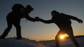De klimmers helpen vriend rek beklimmen van het helpen van hand twee toeristen boven berg Silhouet van reizigers in de winter stock video