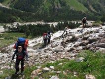 De klimmers kruisen een bergrivier De Kaukasus, Rusland Stock Foto's