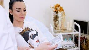 De kliniek, de de kosmetiekruimte, cosmetologist en een mooie jonge patiënt bespreken de procedure van lippenvergroting met stock video
