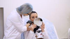 De kliniek, de kosmetiekruimte, het mooie vrouw kijken in de spiegel, de arts bespreekt procedure van de correctie van de lippenv stock video