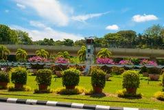 De klockatornet och blommorna, i avståndet kullen för tempel BEM Kanada Miri stad, Borneo, Sarawak, Malaysia Royaltyfri Fotografi