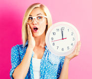 De klok die van de vrouwenholding bijna 12 tonen Stock Afbeelding
