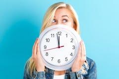 De klok die van de vrouwenholding bijna 12 tonen Royalty-vrije Stock Afbeelding