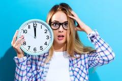 De klok die van de vrouwenholding bijna 12 tonen Royalty-vrije Stock Foto's