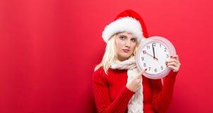 De klok die van de vrouwenholding bijna 12 tonen Stock Fotografie