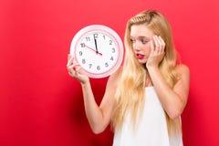 De klok die van de vrouwenholding bijna 12 tonen Royalty-vrije Stock Afbeeldingen