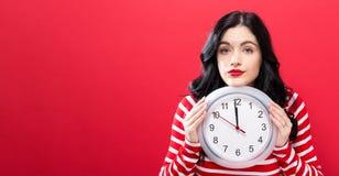 De klok die van de vrouwenholding bijna 12 tonen Stock Foto's