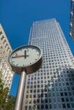 De klok en de wolkenkrabbers van Canary Wharf in het financiële centrum Stock Foto's