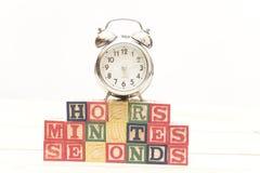 De klok met houten kubussen op de houten uren van lijstwoorden, notulen, seconden koelt stock afbeelding
