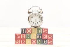 De klok met houten kubussen op de houten uren van lijstwoorden, notulen, seconden koelt stock foto's