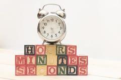 De klok met houten kubussen op de houten uren van lijstwoorden, notulen, seconden koelt stock afbeeldingen