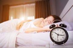 De klok toont 10 am en vrouwenslaap op bed met zonlicht in mor Stock Fotografie