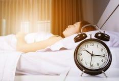 De klok toont 10 am en vrouwenslaap op bed met zonlicht in mor Stock Foto's