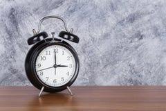 de klok uitstekende klok van 3 o ` op houten lijst en muurachtergrond Stock Afbeeldingen