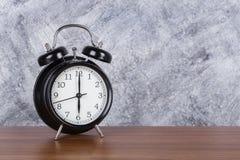 de klok uitstekende klok van 6 o ` op houten lijst en muurachtergrond Stock Afbeeldingen