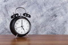 de klok uitstekende klok van 5 o ` op houten lijst en muurachtergrond Stock Fotografie
