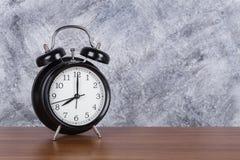de klok uitstekende klok van 8 o ` op houten lijst en muurachtergrond Royalty-vrije Stock Afbeeldingen