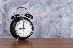 de klok uitstekende klok van 9 o ` op houten lijst en muurachtergrond Stock Foto