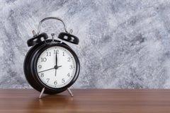 de klok uitstekende klok van 12 o ` op houten lijst en muurachtergrond Stock Fotografie