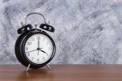 de klok uitstekende klok van 4 o ` op houten lijst en muurachtergrond Stock Afbeeldingen