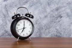 de klok uitstekende klok van 7 o ` op houten lijst en muurachtergrond Stock Afbeeldingen